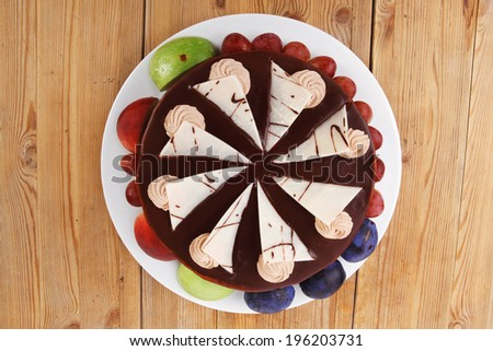 chocolate cream brownie cake topped with white chocolate slice and cream flowers decorated with fruits apple plum and grape on plate on wooden table - stock photo