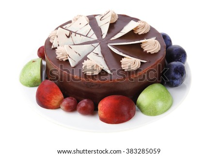 chocolate cream brownie cake topped with white chocolate slice and cream flowers decorated with fruits apple plum and grape on plate isolated over white background - stock photo
