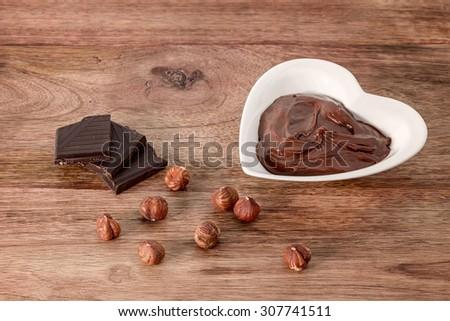 chocolate cream, hazelnut and chocolate on wooden table - stock photo