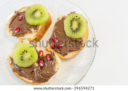 Chocolate cream on homemade bread with fruits on top - stock photo