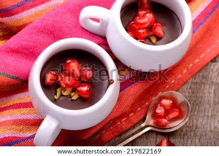 chocolate cream with pomegranate seeds on a wooden table with bright red autumn leaves - stock photo