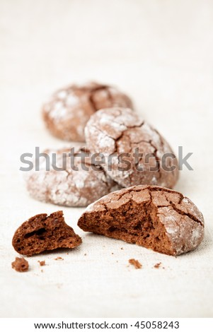 Chocolate crinkles cookies on a linen cloth, shallow dof. - stock photo