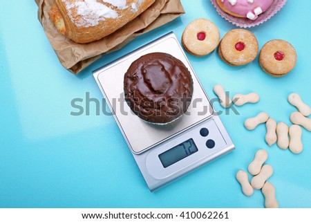 Chocolate cupcake and digital kitchen scales on blue background - stock photo