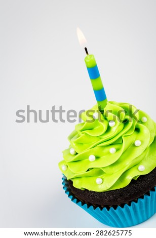 Chocolate Cupcake decorated with green icing, sprinkles and a lit birthday candle on a white background. - stock photo