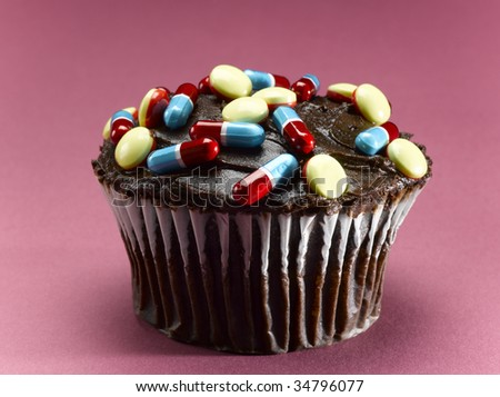 Chocolate cupcake decorated with pills, close-up