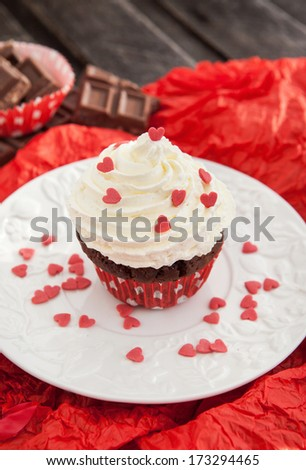 Chocolate cupcake decorated with whipped cream and sugar red hearts