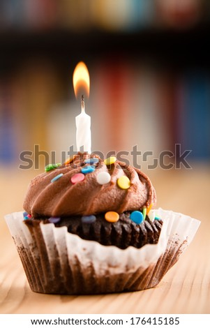 Chocolate Cupcake - This is a shot of a delicious birthday cupcake with a candle sitting on a wooden table top. Shot with a shallow depth of field with the focus on the candle. - stock photo