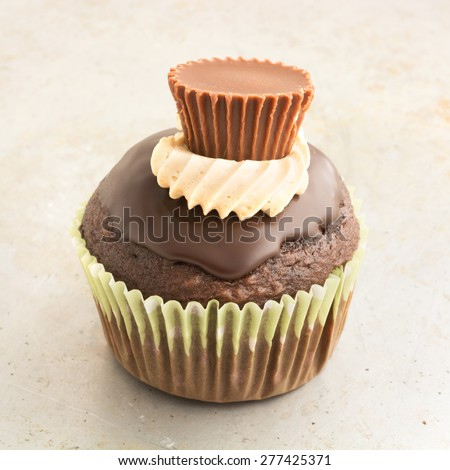 Chocolate cupcake topped with frosting and a peanut butter cup mini. - stock photo