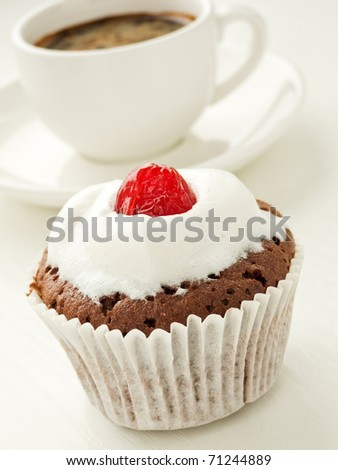 Chocolate cupcake with cherry and coffee cup. Shallow dof. - stock photo