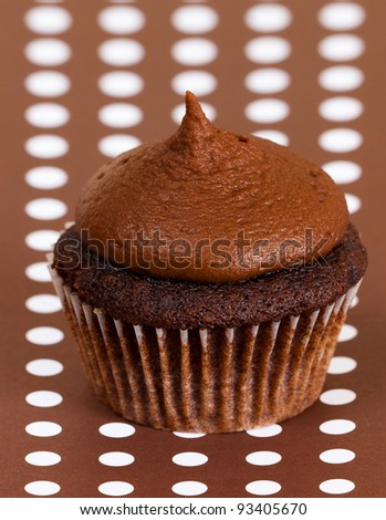Chocolate cupcake with chocolate frosting on brown and white polka dot background - color theme - stock photo