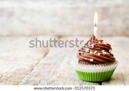 chocolate cupcake with colorful sprinkles with candles. the toning. selective focus. - stock photo