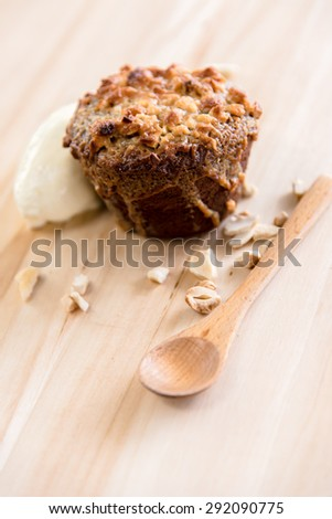 chocolate cupcake with toffee and peanuts on wooden background. - stock photo
