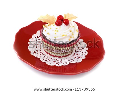 Chocolate cupcake with vanilla frosting decorated with red candy and fondant gold leaves. - stock photo