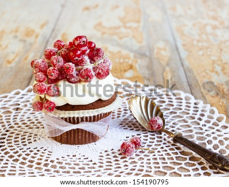 Chocolate cupcake with white frosting and sugared redcurrants. Selective focus - stock photo