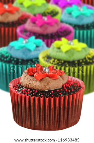 Chocolate cupcakes in colorful cups - very shallow depth of field - stock photo