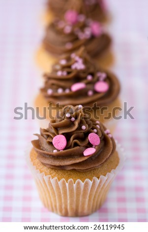 Chocolate cupcakes on a pink gingham tablecloth