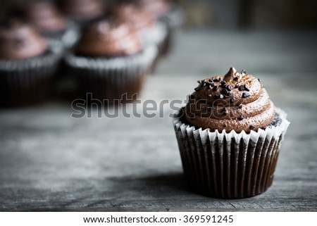 Chocolate cupcakes on rustic wooden background - stock photo