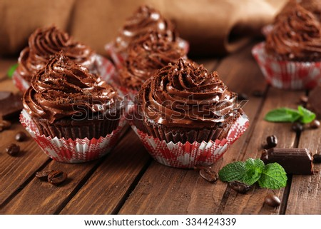 Chocolate cupcakes on wooden background closeup - stock photo