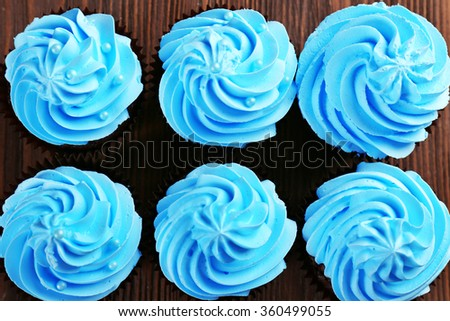 Chocolate cupcakes on wooden background, top view - stock photo