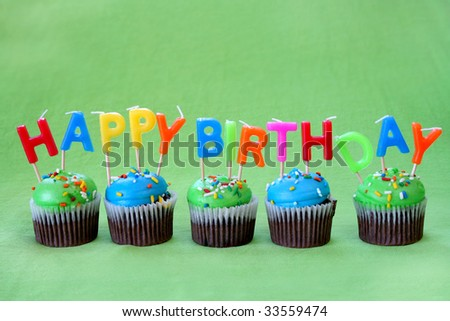 Chocolate cupcakes with blue and green icing along with candles that spell out Happy Birthday. - stock photo