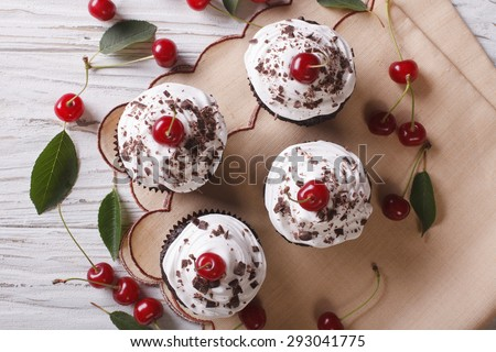 Chocolate cupcakes with cream and fresh cherry Black Forest close up on the table. horizontal top view  - stock photo