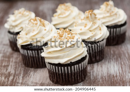 Chocolate cupcakes with vanilla butter cream frosting and gold sprinkles - stock photo