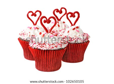 Chocolate cupcakes with vanilla frosting decorated with hearts and sprinkles - stock photo