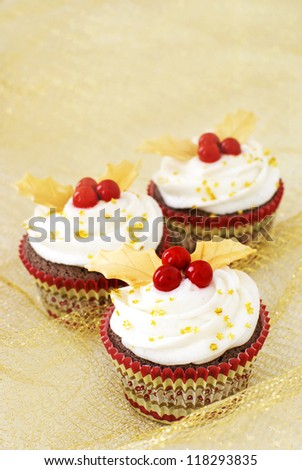 Chocolate cupcakes with vanilla icing and red candy berries and gold fondant leaves - stock photo