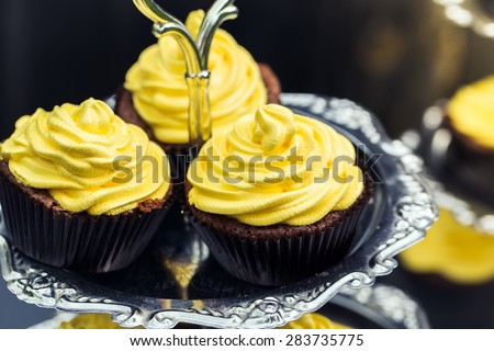 Chocolate cupcakes with yellow frosting and candy sprinkles - stock photo