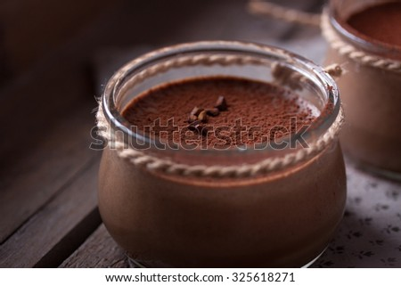 Chocolate dessert in a small glass jar in a wooden box - stock photo