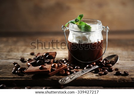 Chocolate dessert in glass with whipped cream on wooden background