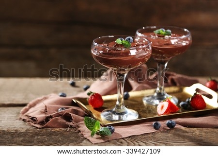 Chocolate dessert in glasses and fresh berries on color wooden background - stock photo