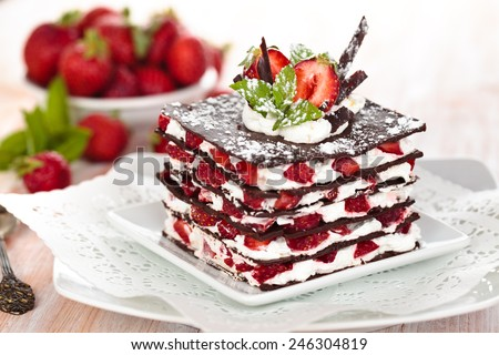 Chocolate dessert with strawberries, whipped cream and mint. - stock photo