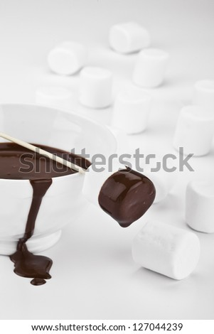 Chocolate Dipped Marshmallows with scattered white mallows on white - stock photo