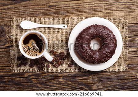 Chocolate donut and cup of hot coffee on vintage wooden background. Top view - stock photo