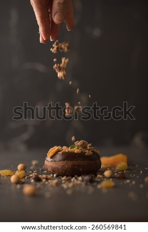 Chocolate Donut sprinkled with crumbs on dark stone background  - stock photo