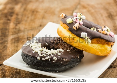 Chocolate donut with Sprinkles on white plate. - stock photo
