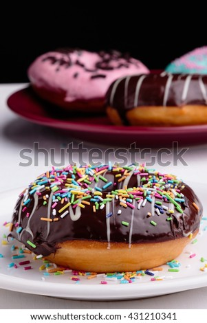 chocolate donut with sprinkles on white plate - stock photo
