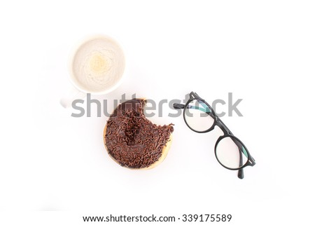 chocolate doughnut been eaten concept with spectacles and a hot drink in the frame - stock photo
