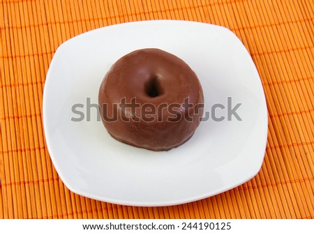 Chocolate doughnut, donut in a white dish - stock photo