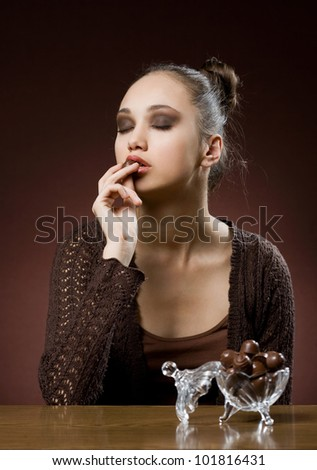 Chocolate dreams, artistic portrait of brunette eating bonbons.
