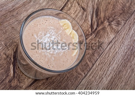 Chocolate drink with coconut and banana on a wooden background - stock photo