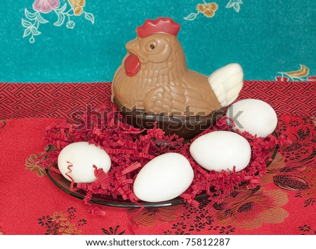 Chocolate Easter chicken and sugar eggs, on  a colorful background