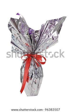 chocolate easter egg in glossy pack with red ribbon, isolated on white - stock photo
