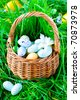 chocolate Easter Eggs in a basket on a green grass - stock photo