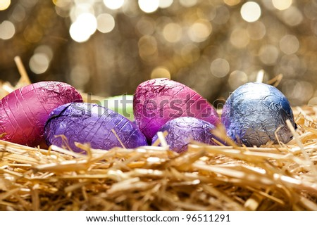 Chocolate Easter eggs in a natural straw nest in front of a beautiful golden background - stock photo