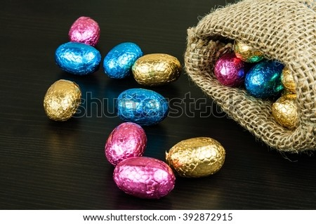 Chocolate Easter eggs in colorful foil on dark background scattered from small jute bag - stock photo