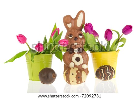 Chocolate easter hare with a bucket pink tulips in spring - stock photo