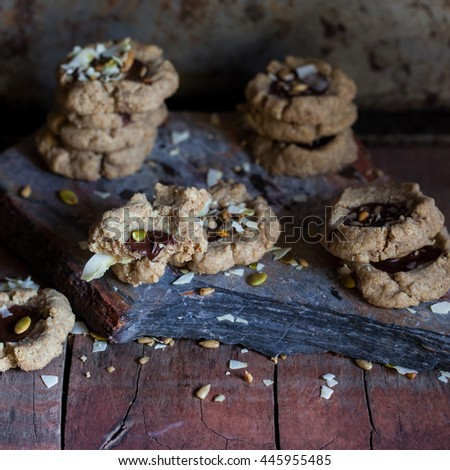 Chocolate filled cookies made of different healthy flours with seeds and nuts. Dark photo. Selective focus. Also available in horizontal format. - stock photo