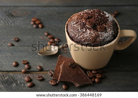 Chocolate fondant cake in cup on wooden background - stock photo